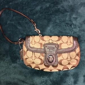 Coach brown signature wristlet with a buckle